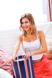 Smiling pregnant woman opening shopping bag Stock Images