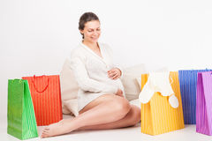 Smiling pregnant woman  opening shopping bag Stock Photography
