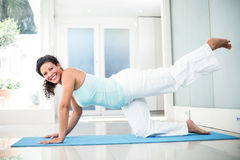 Smiling pregnant woman performing yoga on mat Stock Photo