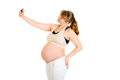 Smiling pregnant woman photographing herself Royalty Free Stock Photography