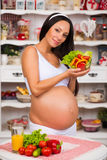 Smiling pregnant woman with a plate of fresh vegetable salad. Stock Images