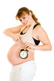 Smiling pregnant woman pointing on alarm clock Stock Image