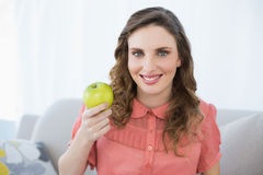 Smiling pregnant woman presenting green apple sitting in living room Royalty Free Stock Images