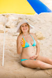 Smiling pregnant woman relaxing on beach and showing suntan loti Stock Photo