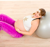 Smiling pregnant woman relaxing after exercising Royalty Free Stock Photo