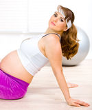 Smiling pregnant woman relaxing after exercising Stock Image