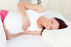 Smiling pregnant woman resting in her bed at home Royalty Free Stock Photography