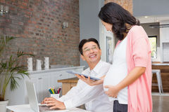Smiling pregnant woman showing tablet to her husband Royalty Free Stock Photos