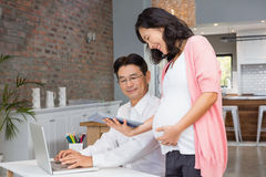 Smiling pregnant woman showing tablet to her husband Royalty Free Stock Image