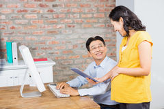 Smiling pregnant woman showing tablet to her husband Stock Photo