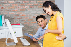 Smiling pregnant woman showing tablet to her husband Stock Image