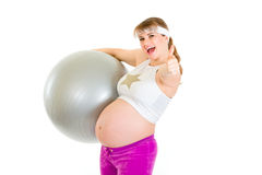 Smiling pregnant woman showing thumbs up gesture Stock Photos