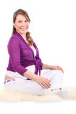 Smiling pregnant woman sits on fur and looks at camera Stock Photography