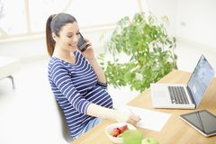 Smiling pregnant woman sitting at desk and making call. Happy young pregnant woman talking with somebody on her mobile phone and writing something while sitting stock image