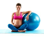 Smiling pregnant woman sitting with fit ball isolated on white background. Concept of healthy life royalty free stock image