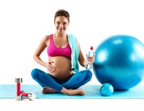 Smiling pregnant woman sitting with fitball isolated on white background. Resting time. Smiling pregnant woman sitting with fitball isolated on white background royalty free stock photography