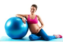 Smiling pregnant woman sitting on mat with fitball isolated on white background. Concept of healthy life stock images