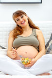 Smiling pregnant woman on sofa with fruit salad Royalty Free Stock Image