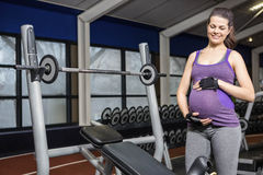 Smiling pregnant woman standing next to bench Royalty Free Stock Photo