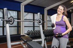 Smiling pregnant woman standing next to bench Stock Photo