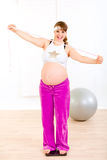 Smiling pregnant woman standing on weight scale Royalty Free Stock Photo