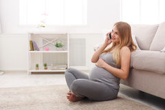 Smiling pregnant woman talking on her smartphone. Happy expectant blonde have pleasant talk on phone and touching her belly, sitting on floor, copy space Stock Images