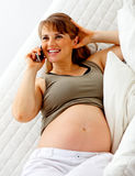 Smiling pregnant woman talking mobile phone Stock Images
