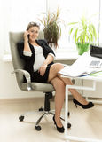 Smiling pregnant woman talking on phone at office Royalty Free Stock Image