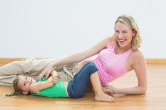 Smiling pregnant woman tickling young daughter looking at camera. Smiling pregnant women tickling young daughter looking at camera in a fitness studio Royalty Free Stock Photography
