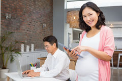 Smiling pregnant woman using tablet Royalty Free Stock Photos