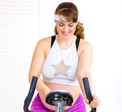 Smiling pregnant woman working out on bicycle Stock Photography