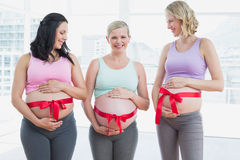 Smiling pregnant women standing with red bow around bumps Royalty Free Stock Images
