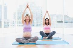 Smiling pregnant women in yoga class sitting in lotus pose Royalty Free Stock Photos