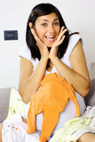 Smiling pregnant young woman with baby clothes Royalty Free Stock Photos