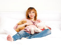 The smiling pregnant young woman on a bed with plush toys Royalty Free Stock Photos