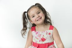Smiling, preschool girl with brown pony tails stock photo