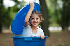 Girl in blue recyling waste bin have fun inside. Concept of environmental protection. Colorful boxes. royalty free stock photography