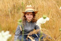 Smiling Preteen country girl with straw hat. A young smiling preteen little girl with long blond hair wearing a hat in a field of tall grass and white wild Queen Royalty Free Stock Photography