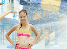 Smiling preteen girl standing under water drops. Blurred waterpa Royalty Free Stock Images