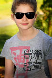 Cool Cute Preteen. Pretty smiling preteen country girl wearing sunglasses, shallow depth of field Stock Images
