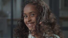 Smiling preteen girl twirling hair on finger playfully