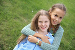 Smiling preteen girls. Outdoors on green grass background Stock Images