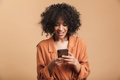 Smiling pretty african woman writing message on smartphone royalty free stock photography