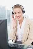 Smiling pretty agent wearing headset dealing with customer Royalty Free Stock Images