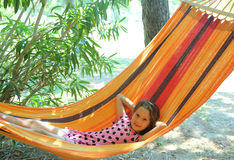 Smiling pretty baby rests in a hammock of the tourist village du Royalty Free Stock Images