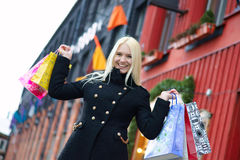 Smiling pretty blond girl with shopping bags Stock Images