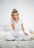 Smiling pretty blonde wearing hair curlers on the phone Stock Photos