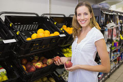 Smiling pretty blonde woman buying an apple Stock Photo