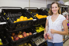 Smiling pretty blonde woman buying apples Royalty Free Stock Photos