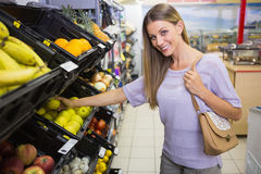 Smiling pretty blonde woman buying apples Royalty Free Stock Images